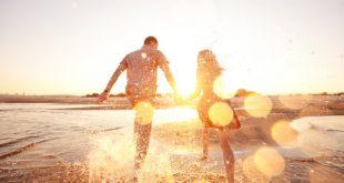 Casal pulando na praia