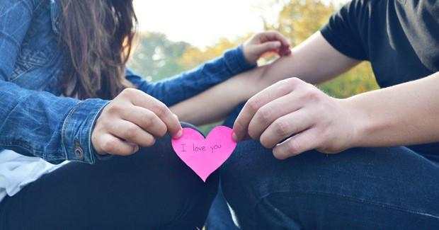 Casal segurando coração de papel